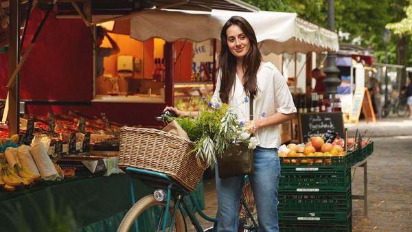 Frau mit Fahrrad steht auf einem Marktplatz. Im Korb transportiert sie Gemüse.