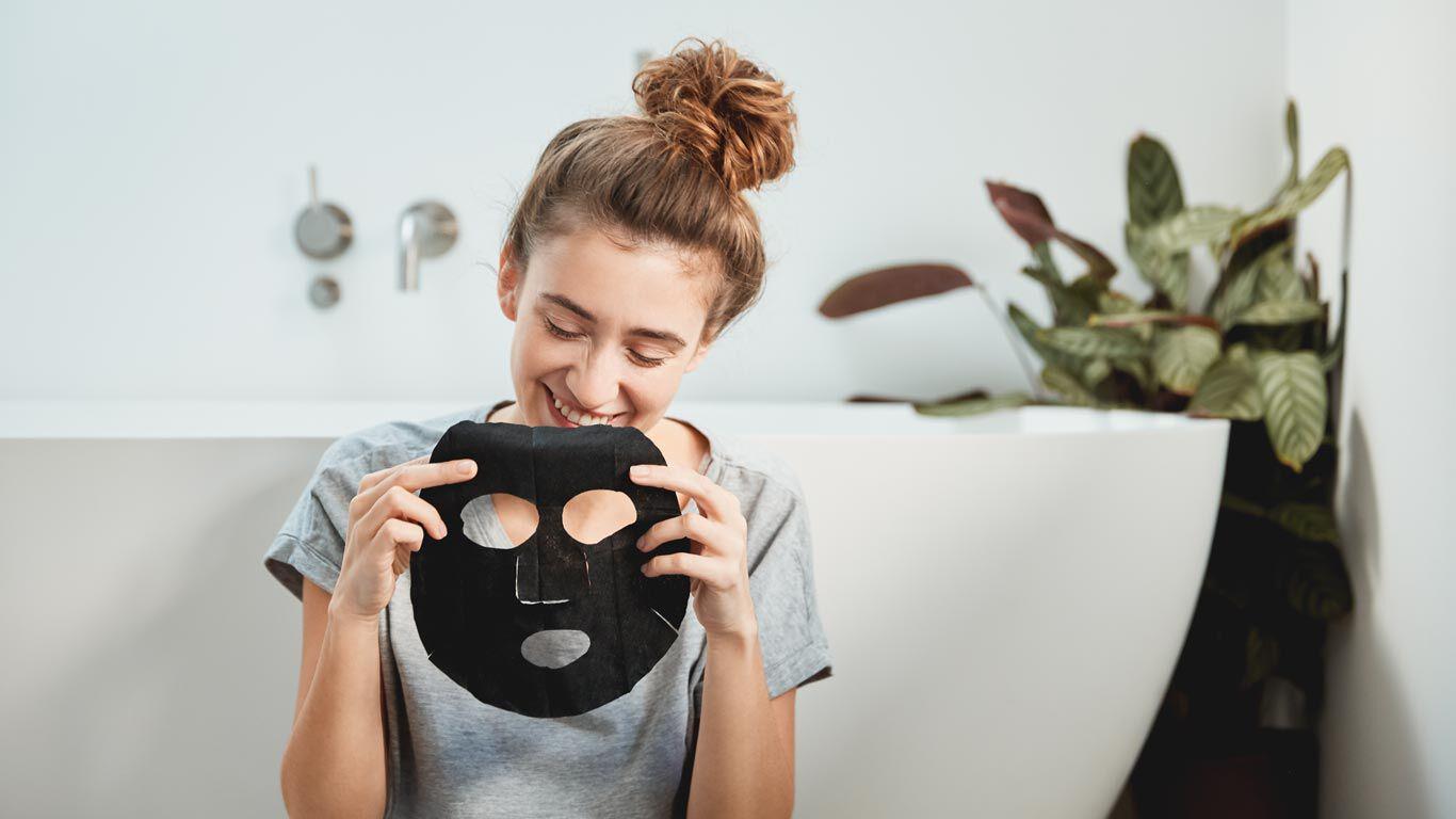 Eine Frau lacht über die schwarze Farbe der Tuchmaske Detox Pflege