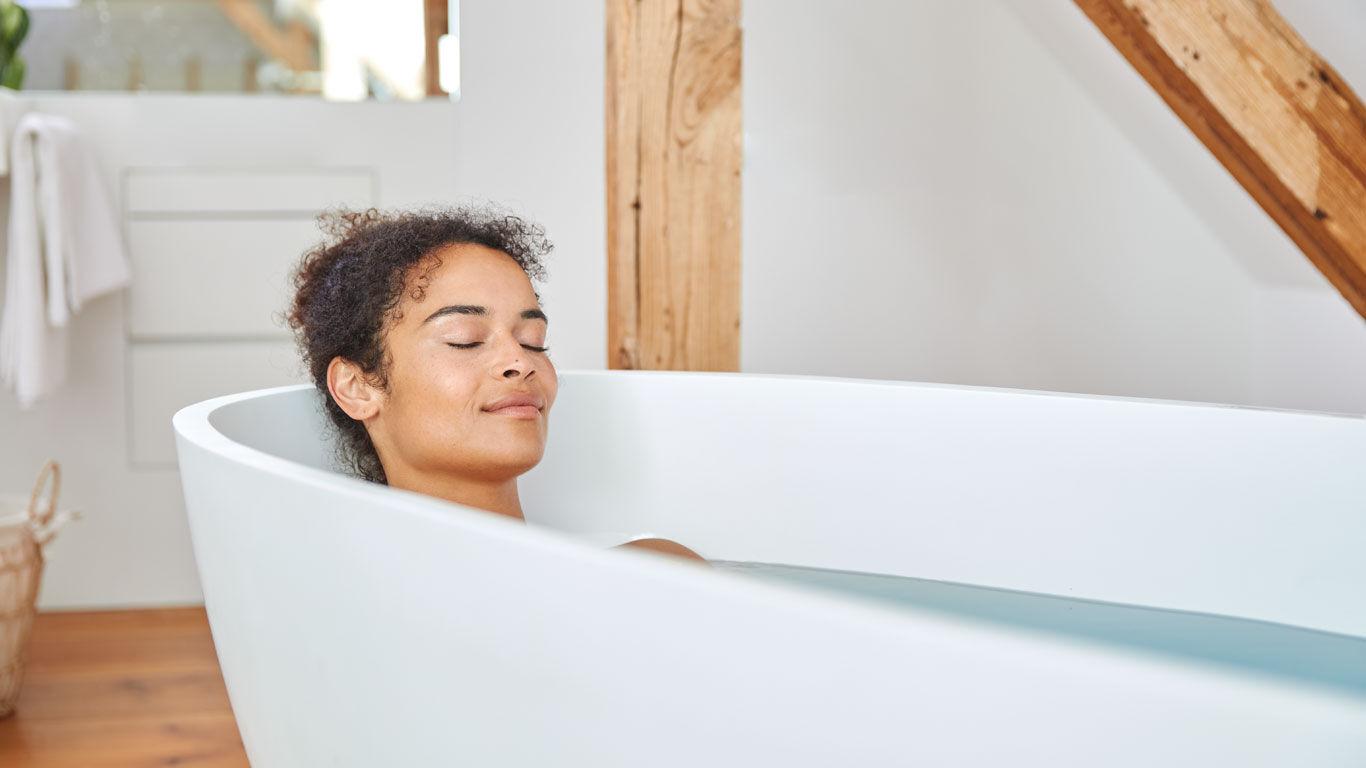 Dunkelhaarige Frau entspannt in der Badewanne.