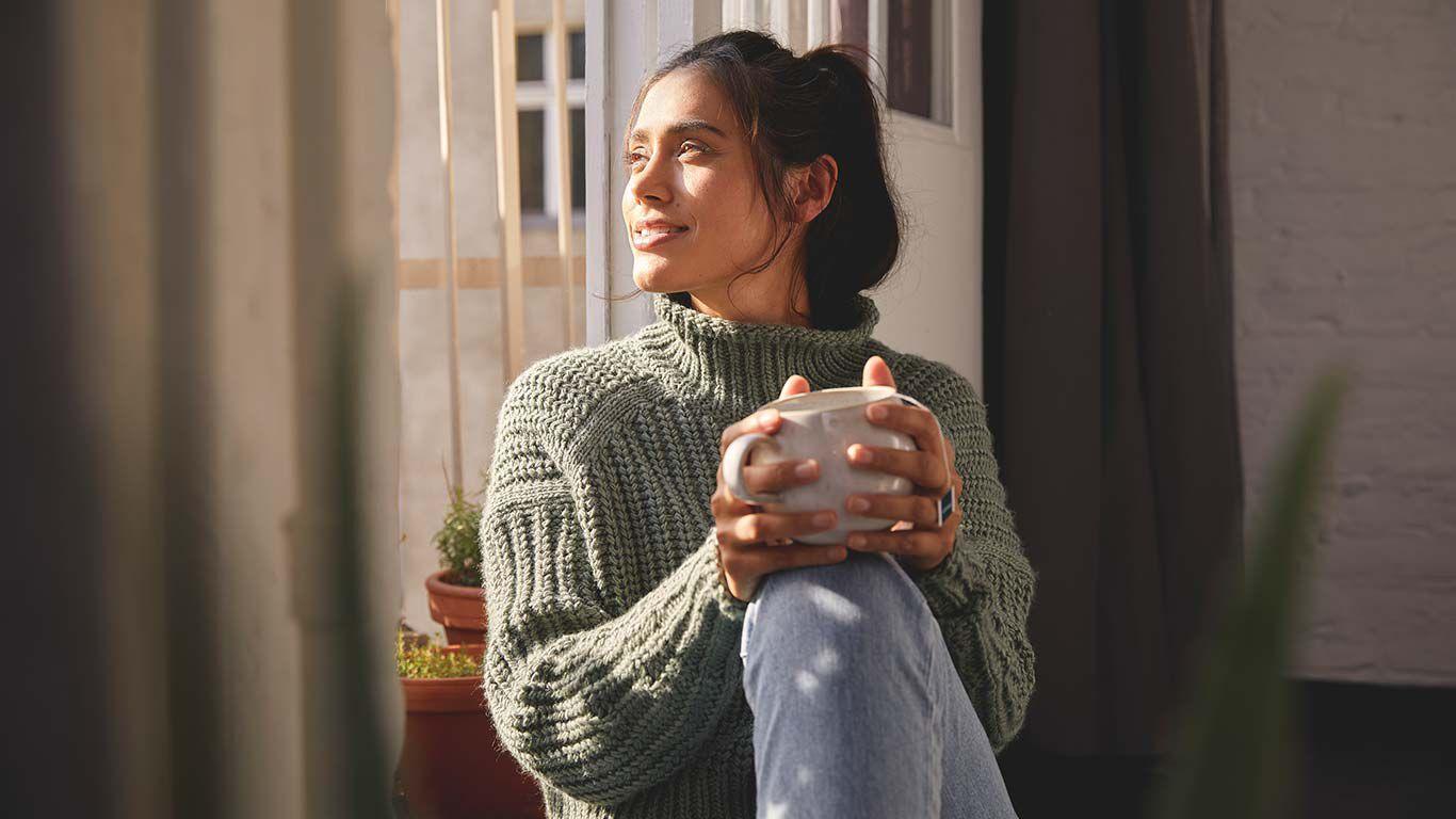 Frau sitzt mit einer Tasse Tee am Fenster und blickt hinaus in die Natur.