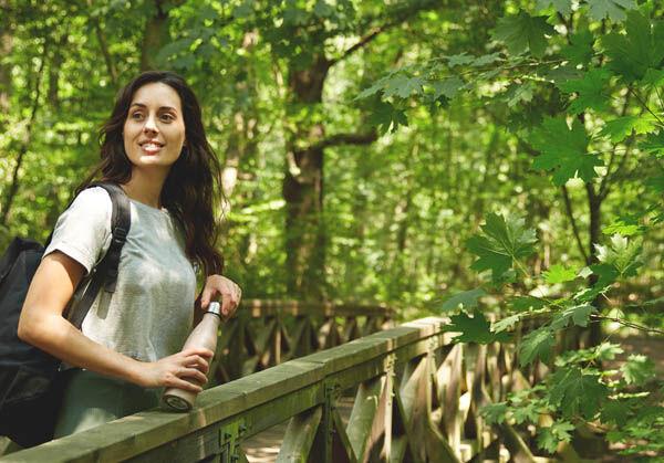 Frau steht im Wald und schaut in die Ferne