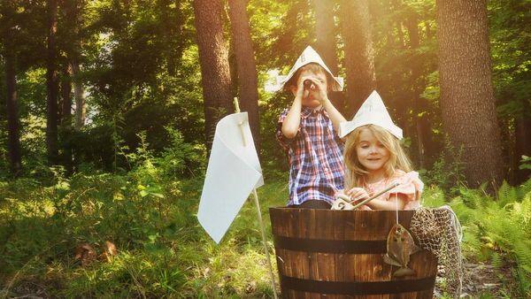Mädchen und Junge in einem Holzfass im Wald beim Piraten-Spielen.