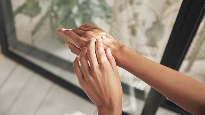 Zwei Hände beim Eincremen.
