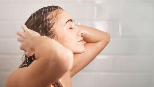 Frau seif sich die Haare unter der Dusche ein.