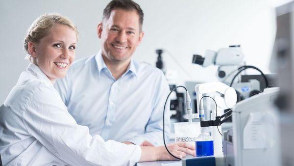 Frau in Laborkittel und Mann im Hemd sitzen vor einem Mikroskop und lachen in die Kamera.