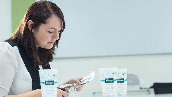 Junge Frau schneidet Designvorlage. Neben ihr stehen Kneipp Produkte.