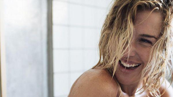 Lachende blonde Frau in der Dusche.