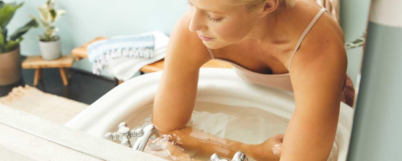 Die Unterarme von einer Frau sind in einem mit Wasser gefüllten Waschbecken.