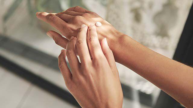 Nahaufnahme von zwei Händen beim Eincremen.