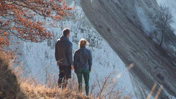 Frau und Mann stehen in der Natur. Bild zeigt Rückansicht der beiden.