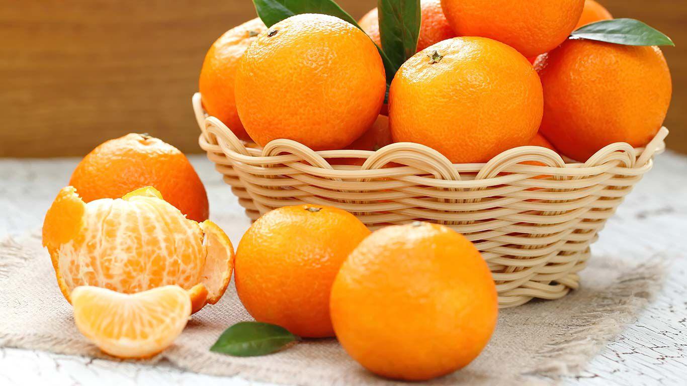 Mandarinen in einem geflochtenen Holzkorb.
