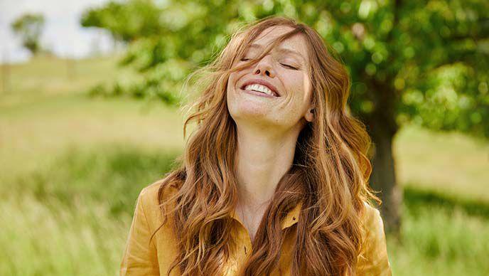 Rothaarige Frau in gelber Bluse steht auf einer grünen Wiese, wirft ihren Kopf in den Nacken und lacht.