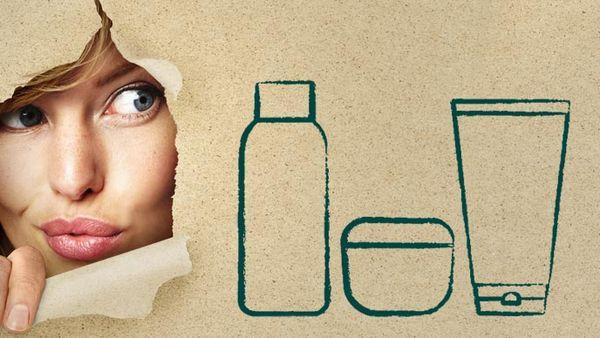 Frau spitzt hinter einem Plakat mit Zeichnung von Produktverpackungen hervor.