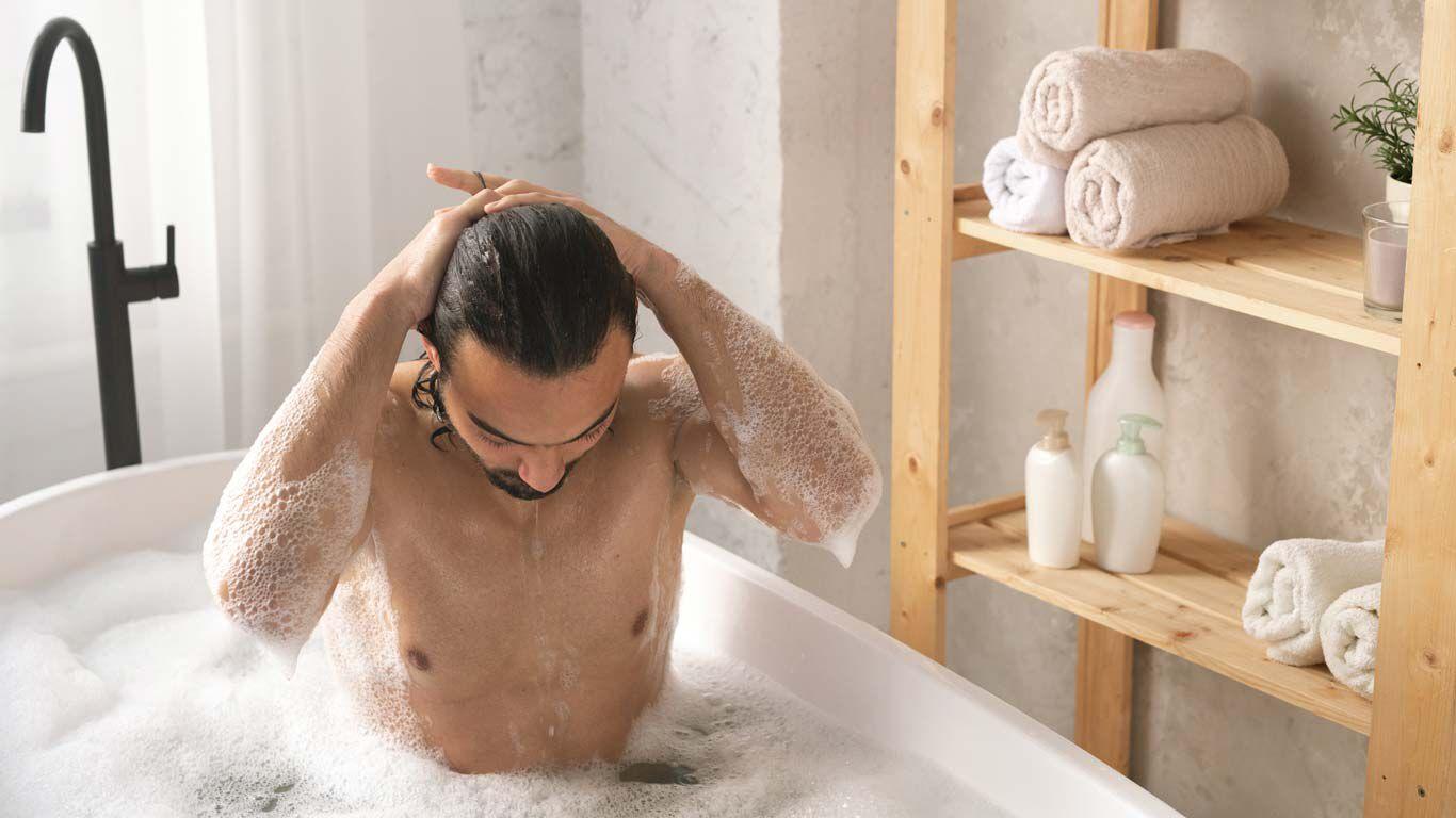 Mann sitzt in der Badewanne und streift sich die Haare zurück.