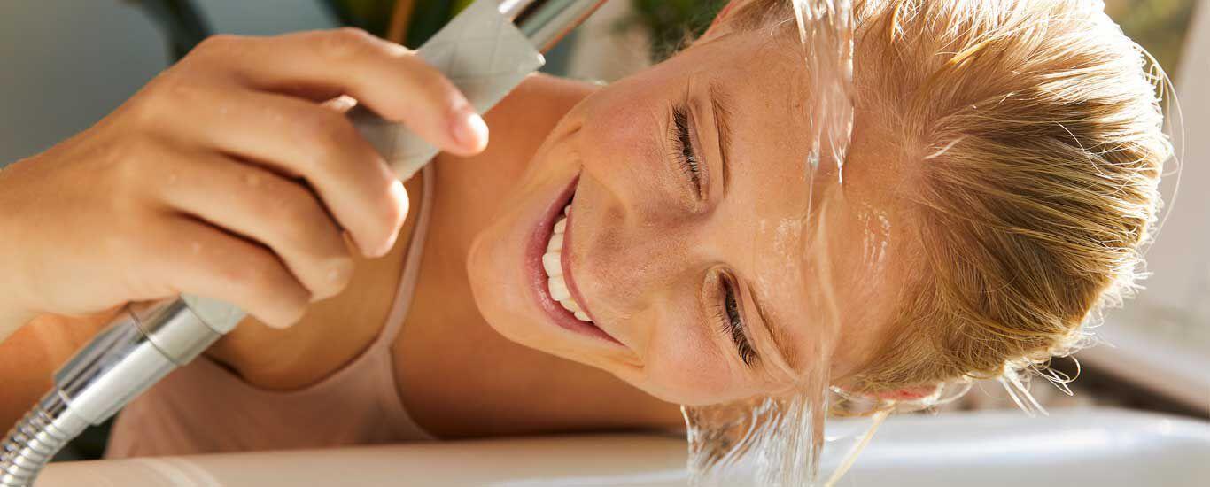 Frau lässt über dem Waschbecken Wasser über ihr Gesicht laufen und lacht dabei.
