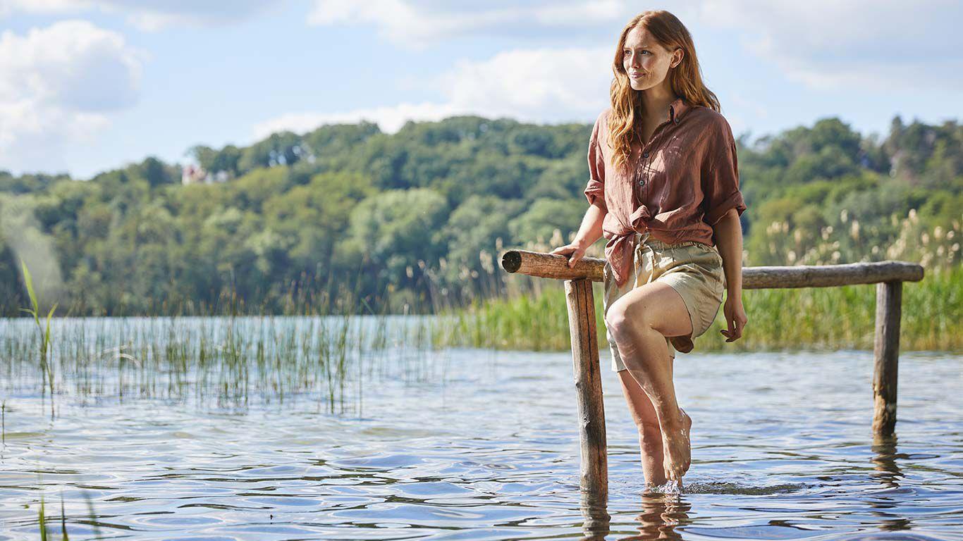 Frau, die in einem See steht und die Kneipp Wasseranwendung Wassertreten durchführt. Blick nach links.