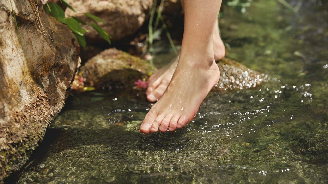 Nahaufnahme von Füßen, einer davon ragt in das Wasser.