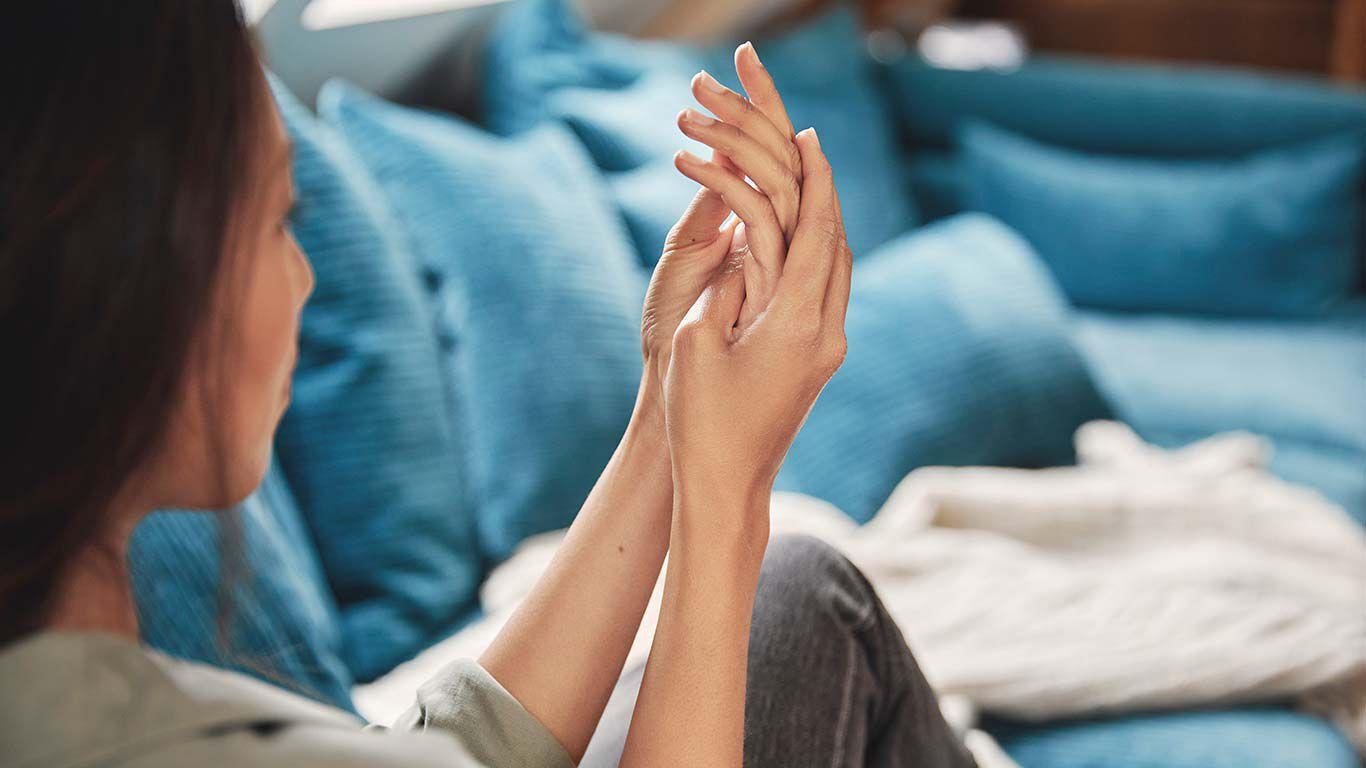 Rückansicht einer dunkelhaarigen Frau, die auf einer blauen Couch sitzt und sich die Hände eincremt.
