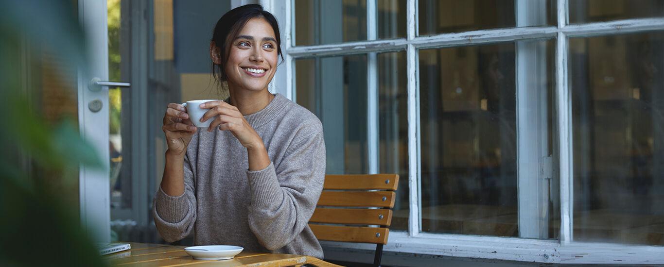 Frau sitzt mit einer Tasse Tee an einem geöffneten Fenster.