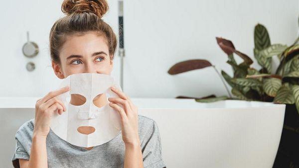 Frau sitzt im Badezimmer und hält eine Tuchmaske lachend vor ihrem Gesicht.