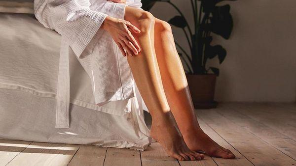 Frau sitzt im Bademantel auf der Bettkante und cremt ihre Beine ein.