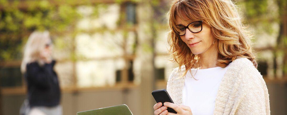Frau mit Brille steht mit ihrem Smartphone im Freien.