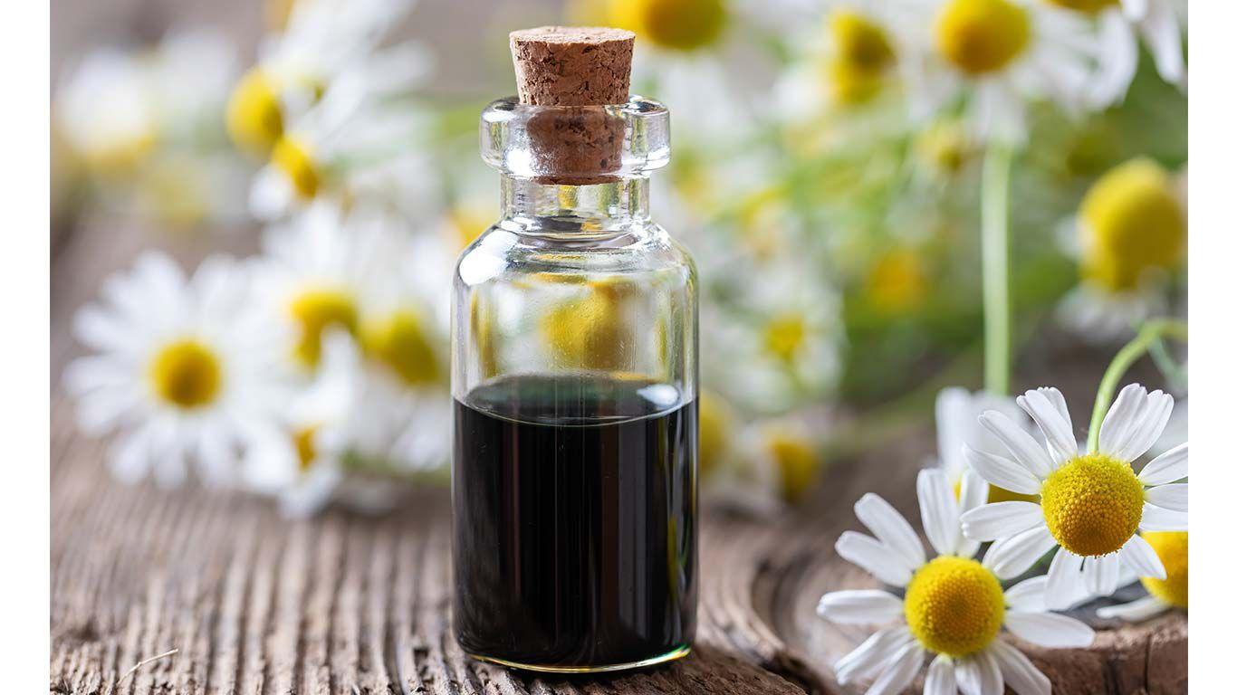 Kamillenöl in Glasflasche auf einem Holztisch. Daneben Kamillenblüten.