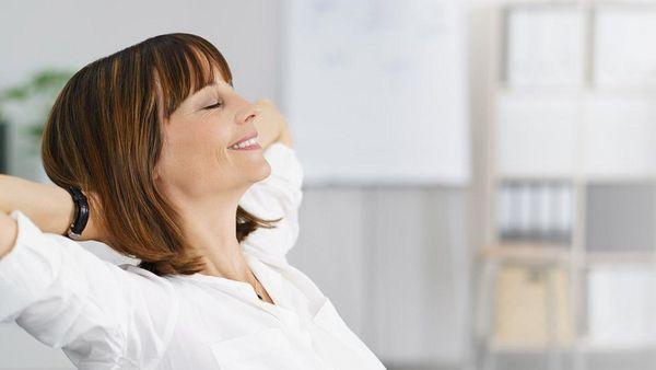 Frau verschränkt ihre Arme hinter dem Kopf und lehnt sich lächelnd auf einem Stuhl zurück.