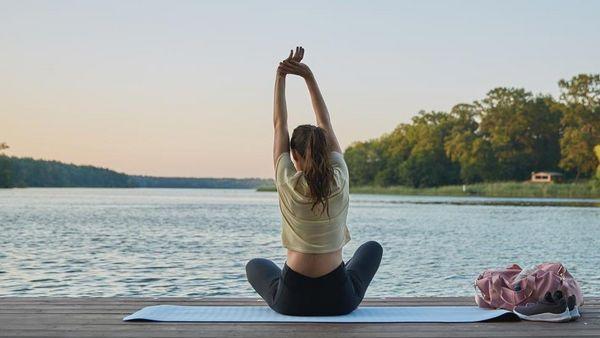 Frau sitzt auf einer Yogamatte auf einem Steg und dehnt sich.