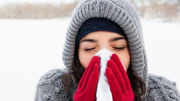 Frau in dicken Winterklamotten putzt sich die Nase.