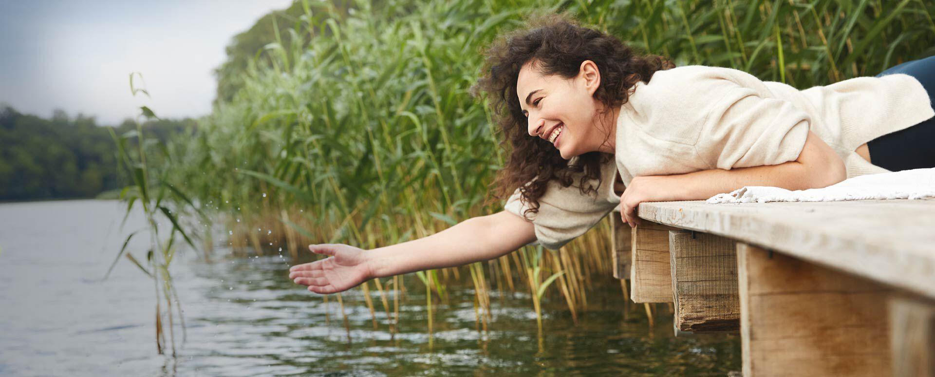 Sebastian Kneipps Erkenntnisse sind heute relevant wie nie. Auf dem Bild genießt eine Frau das kühle Wasser eines Sees.