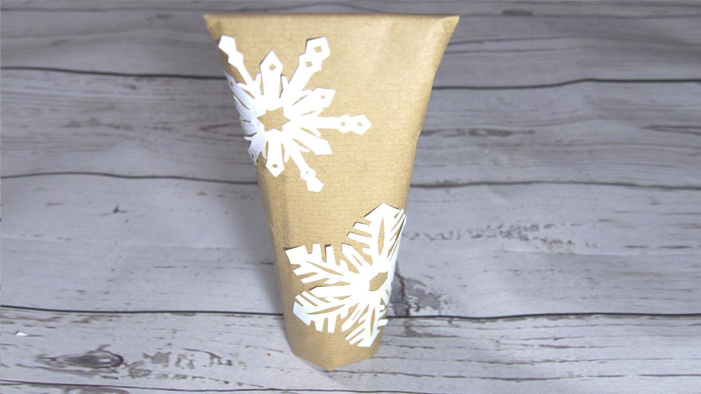 Schritt 7: Mit einem Klebestift die Schneeflocken auf das verpackte Geschenk kleben.