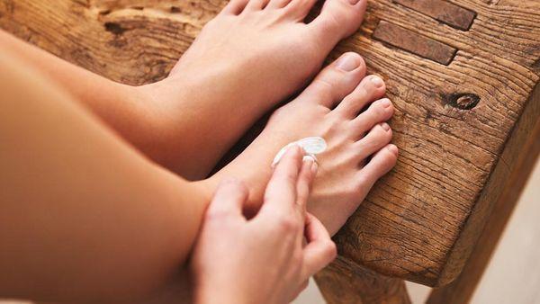 Füße auf einem Holzhocker, die eingecremt werden.