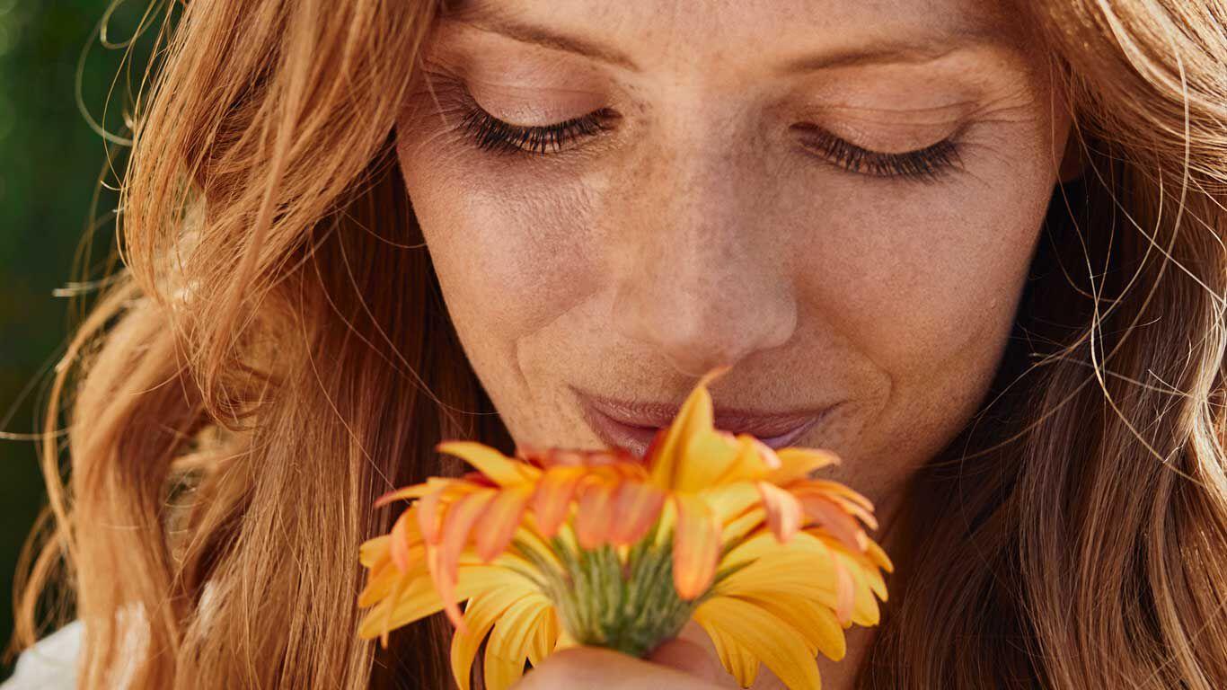 Eine junge Frau riecht an einer Calendula-Blüte.
