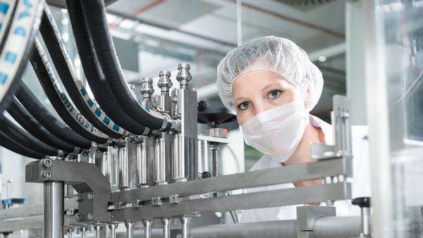 Frau in Hygienekleidung zwischen Maschinen.