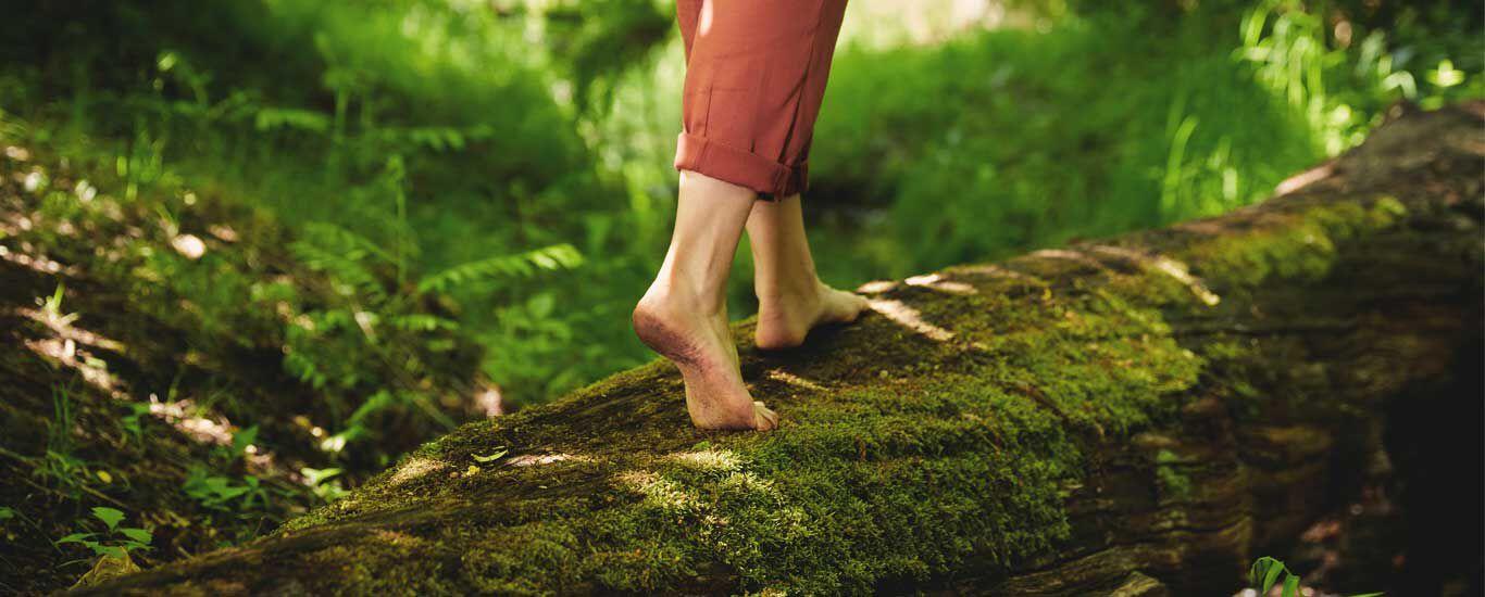 Frau läuft auf einem Baumstamm im Wald, wobei das Bild aus einer Nahaufnahme von ihren Füßen besteht.