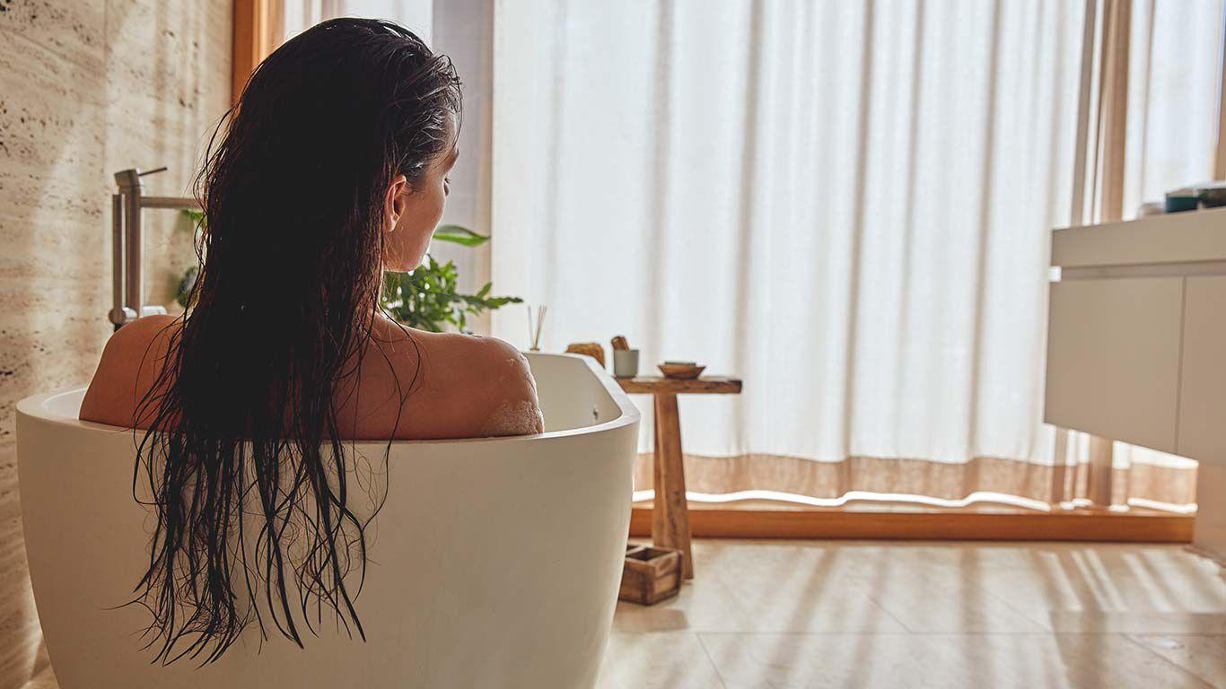 Frau mit langen braunen Haaren entspannt in einer Badewanne. Ansicht von hinten.