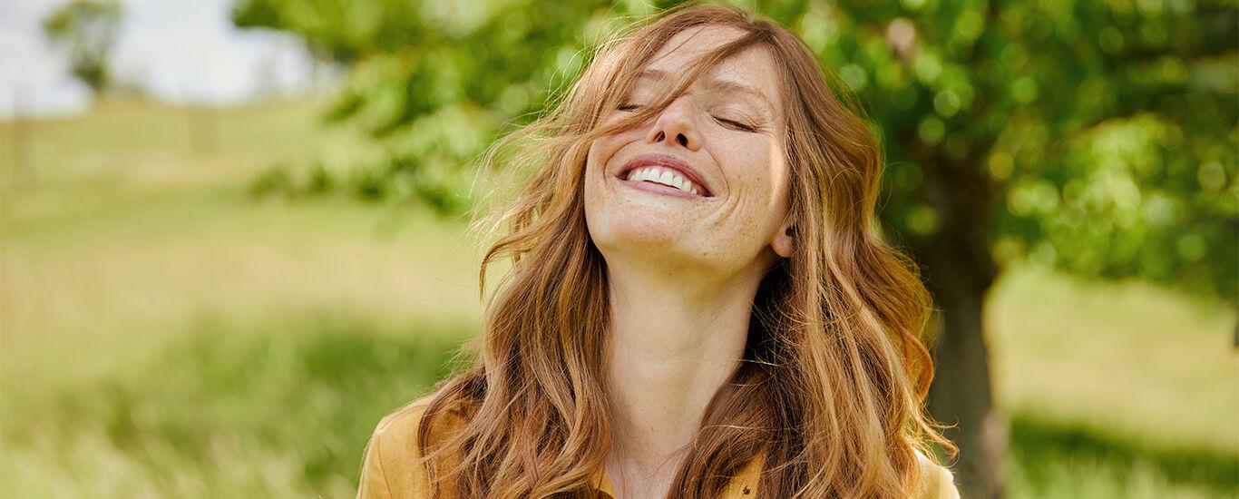 Frau mit roten langen Haaren wirft den Kopf in den Nacken und lacht herzlich