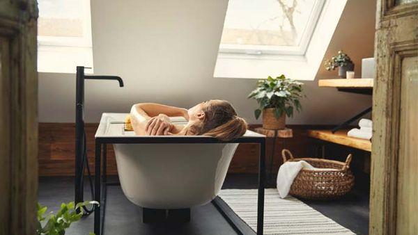 Rückansicht einer Frau in der Badewanne.