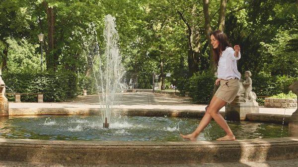 Dunkelhaarige Frau balanciert auf dem Rand eines Springbrunnens.