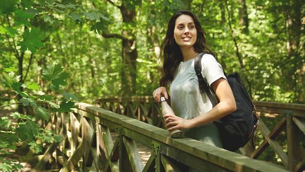 Frau macht an einer Holzbrücke im Wald Pause und genießt die Natur.
