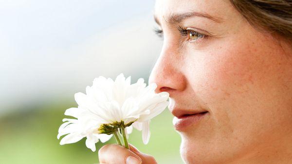 Frau riecht an weißer Blüte.