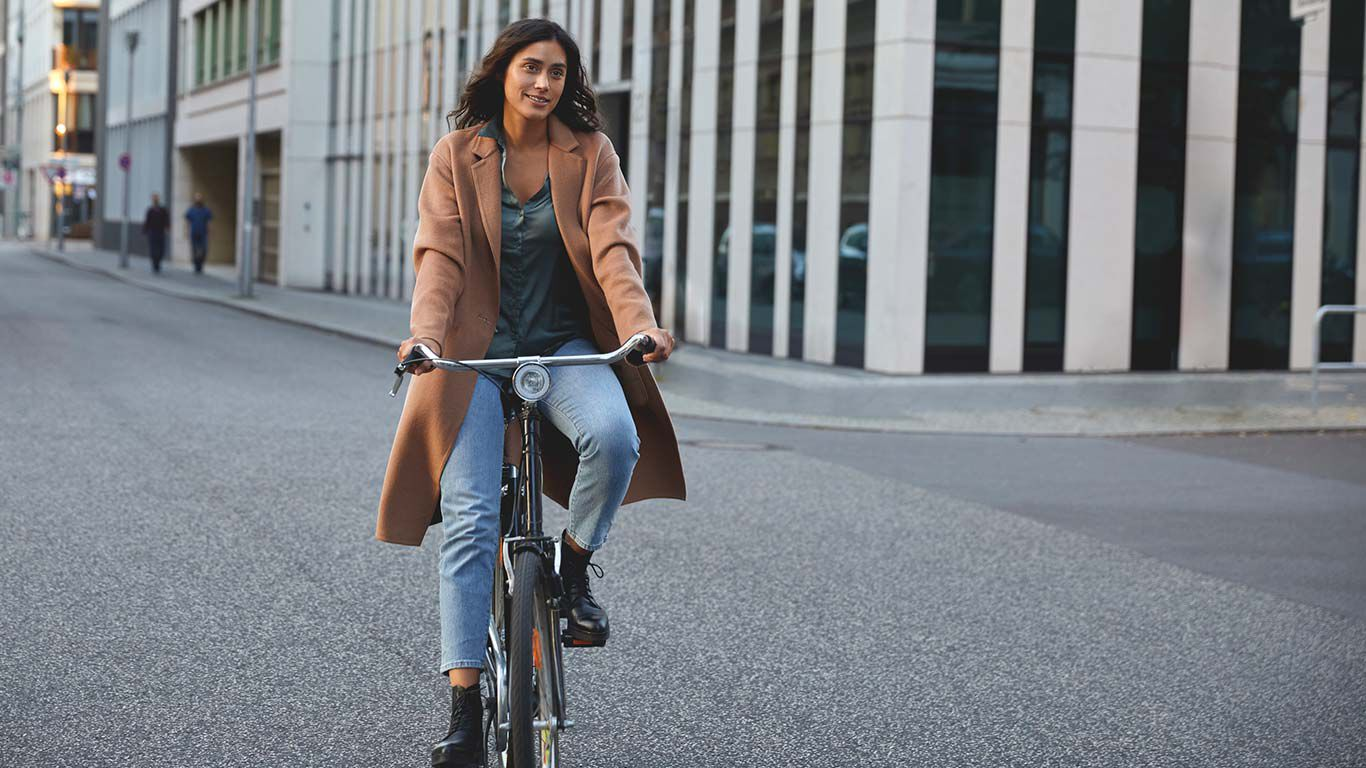 Frau in Businessklamotten fährt auf einem Fahrrad durch die Stadt.