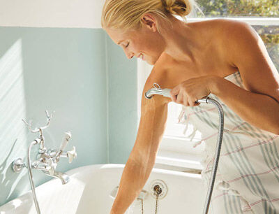 Eine Frau beim Armguss an der Badewanne