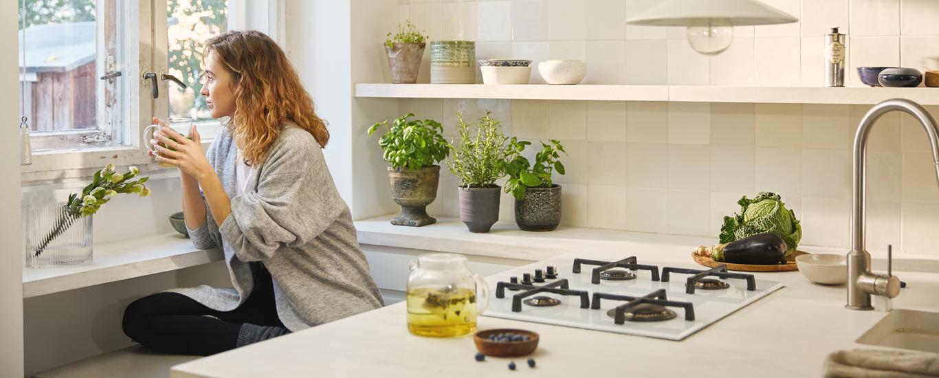 Junge Frau trinkt Tee und sieht aus dem Fenster.