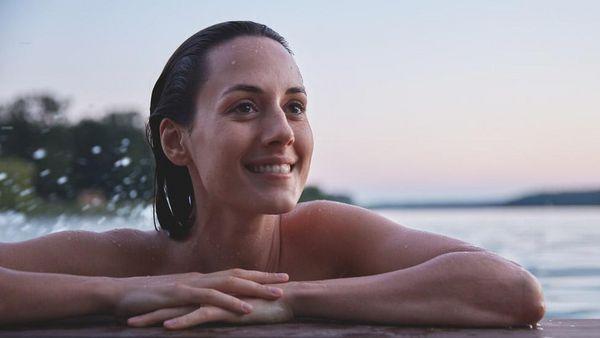 Frau im Wasser stützt sich auf einem Steg am See ab.