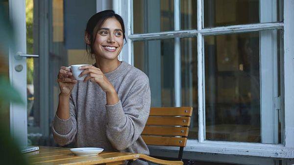 Frau sitzt mit einer Tasse Heißgetränk auf einem Holzstuhl bei geöffnetem Fenster.