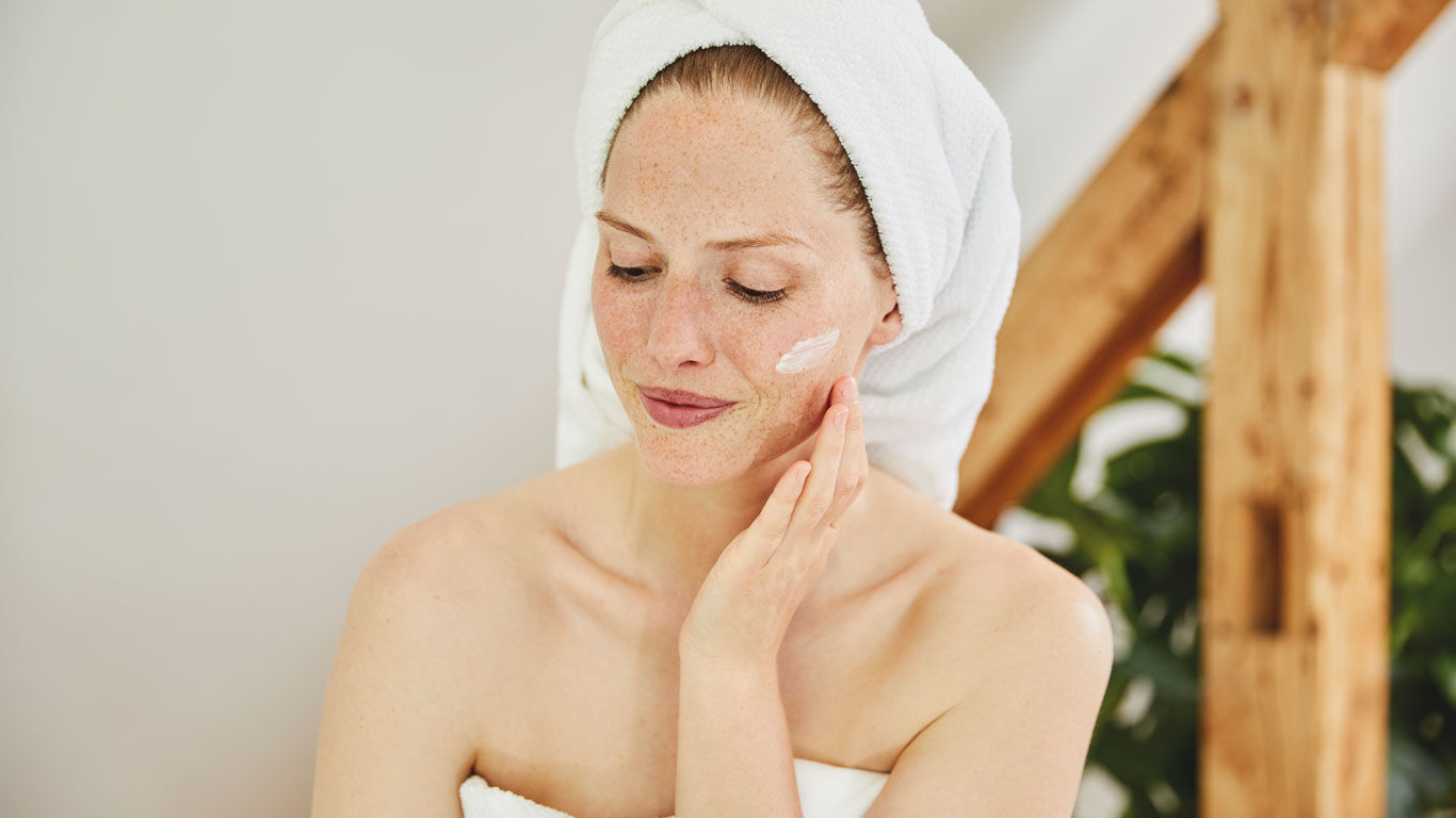 Junge Frau cremt sich das Gesicht mit Feuchtigkeitscreme ein