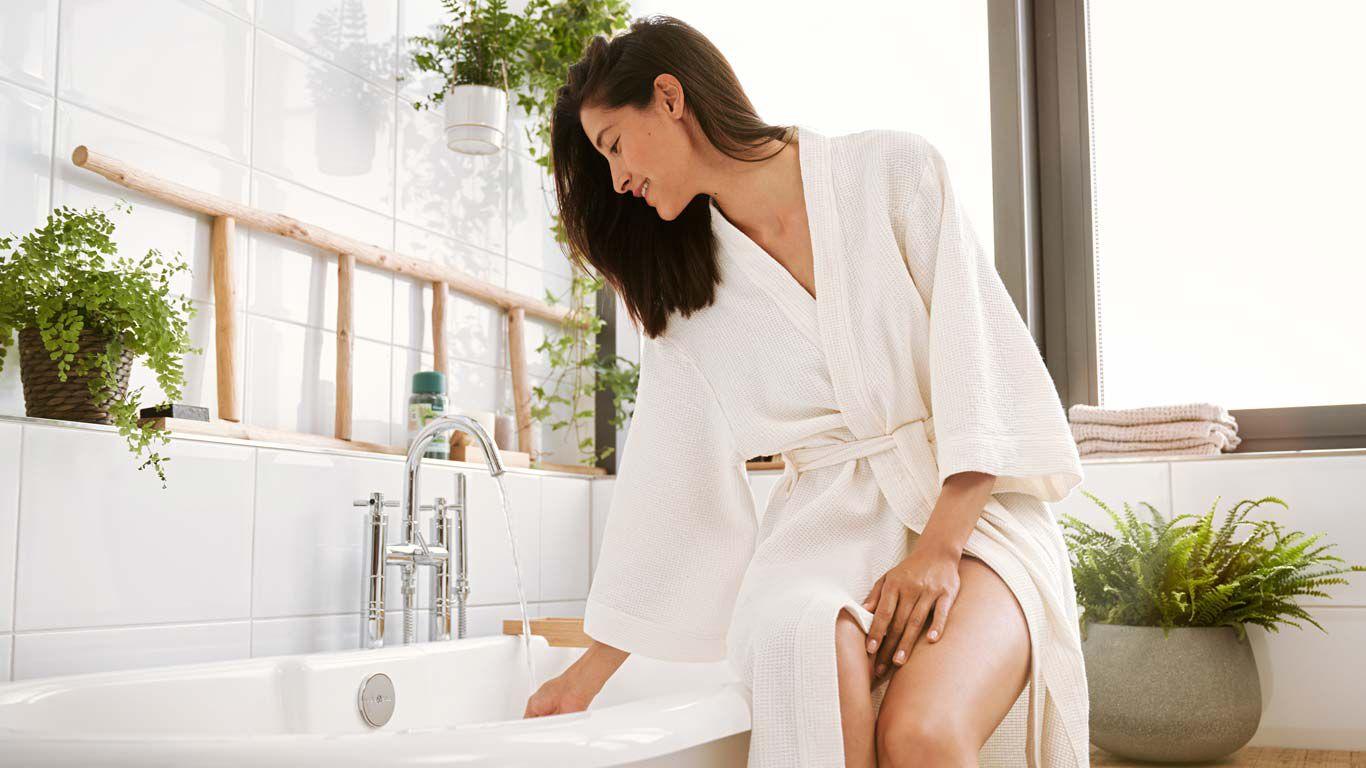 Frau lässt Badewasser ein und genießt den Duft.