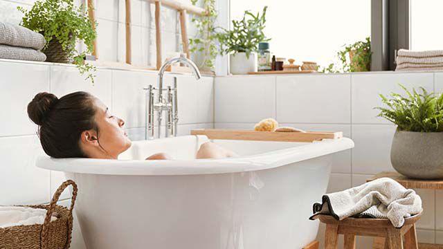 Frau liegt in der Badewanne und entspannt.